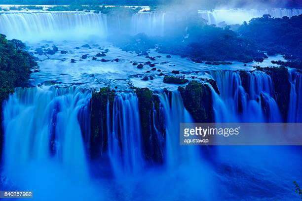 Impressive Iguacu falls landscape, blurred motion from long exposure at dramatic sunset - Idyllic Devil's Throat - international border of Brazilian Foz do Iguacu, Parana, Argentina Puerto Iguazu, Misiones and Paraguay - South America