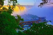 Impressive Iguacu falls landscape, blurred motion from long exposure at dramatic sunset - Idyllic Devil's Throat - international border of Brazilian Foz do Iguacu, Parana, Argentina Puerto Iguazu, Mis