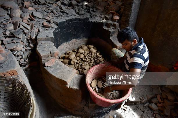 Imran puts earthen lamps inside a furnace at Pottery Town on October 12 2017 in Bengaluru India Pottery Town is a patch of clay amid the City of...