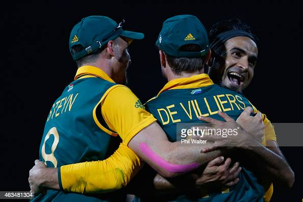 Imran Tahir of South Africa hugs AB de Villiers of South Africa after dismissing Tinashe Panyangara of Zimbabwe during the 2015 ICC Cricket World Cup...