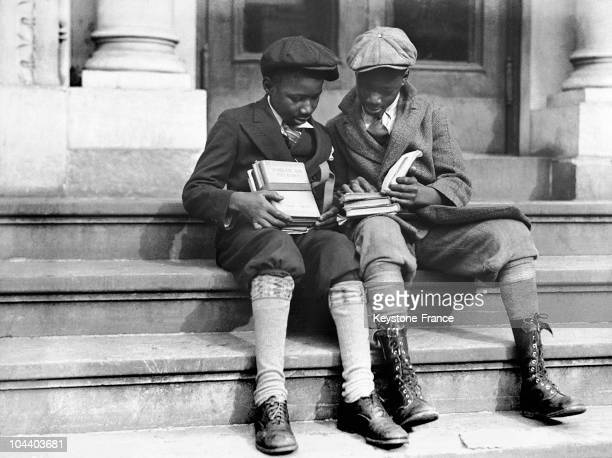 In 1933 in Harlem New York two black children seated on the sidewalk look at their schoolbooks One of the books concerns American history