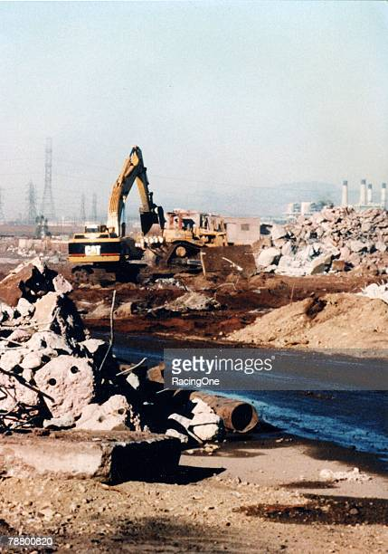 In 1995 a Caterpillar excavator and a tractor clear the remains of a former steel mill on the site of the new California Speedway in Fontana...