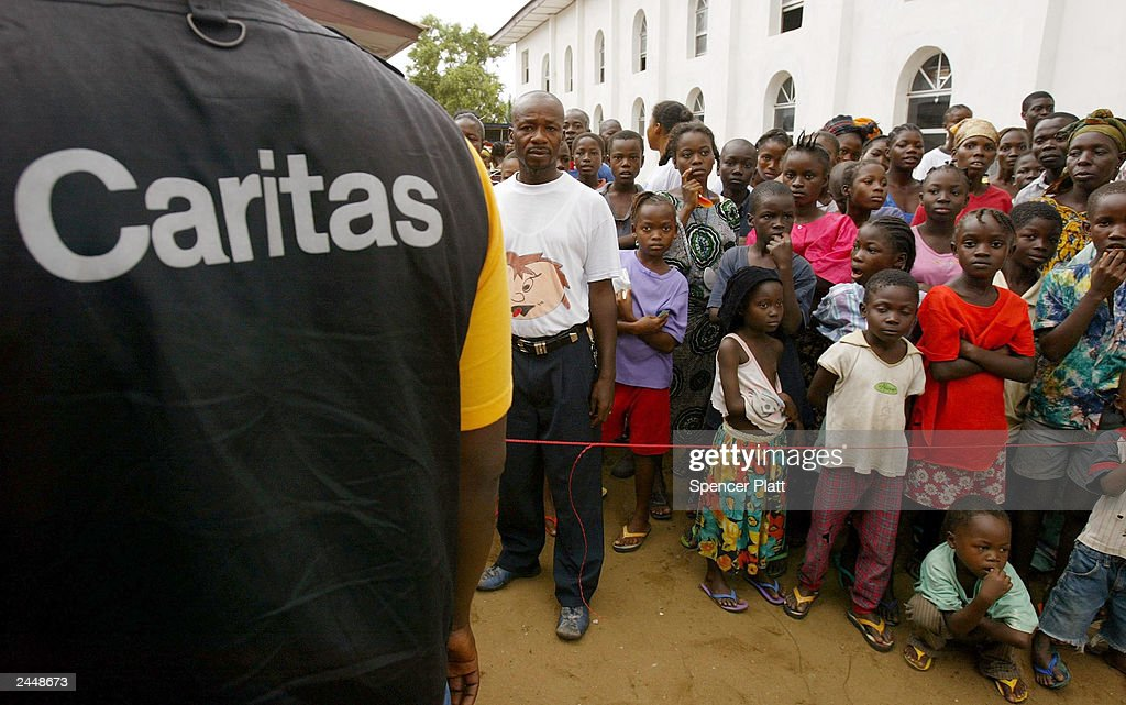 In a camp for those displaced by war people receive relief items by the aid group Caritas August 30 2003 in Monrovia Liberia After a month of heavy...