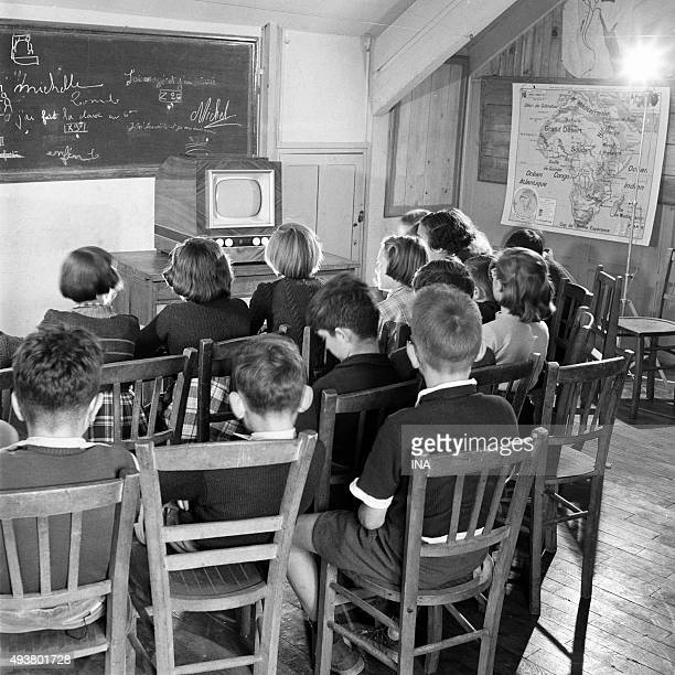 In a class schoolboys in front of a television set