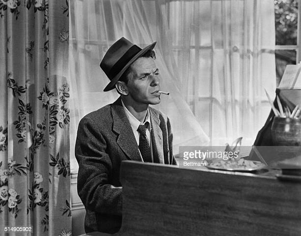 In a classic pose Frank Sinatra smokes a cigarette as he plays piano in the movie Young at Heart One of the movie's songs became a trademark 'saloon...