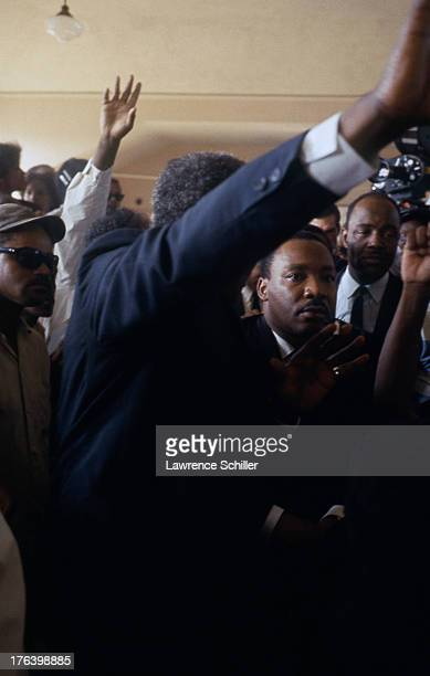 In a crowded room American Civil Rights and religious leader Dr Martin Luther King Jr listens to an unseen speaker during the Watts riots Los Angeles...