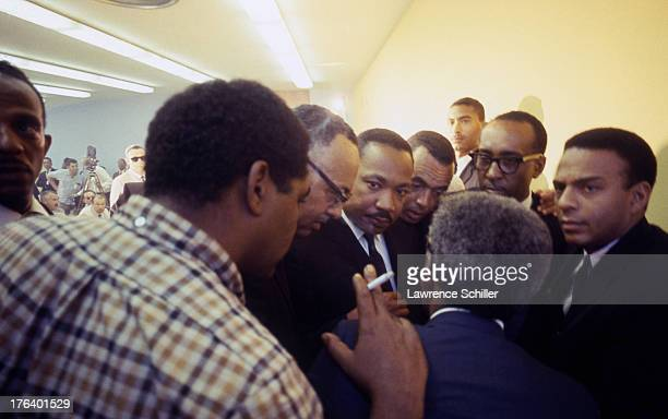 In a crowded room American Civil Rights and religious leader Dr Martin Luther King Jr listens to unidentified advisors during the Watts riots Los...
