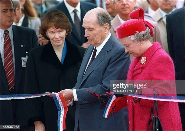 In a file picture taken on May 6 1994 French President François Mitterrand and Britain's Queen Elizabeth II cut a ribbon as Mitterand's wife Danielle...