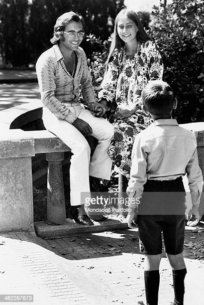 In a garden seated on a balustrade the Italian singer Al Bano born Albano Carrisi and his young wife Romina Power are holding hands smiling to a boy...