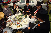 In a grassy car park on Ladies Day at Royal Ascot racing week a group of men talk and relax one smoking a cigar surrounded by the remains of a...