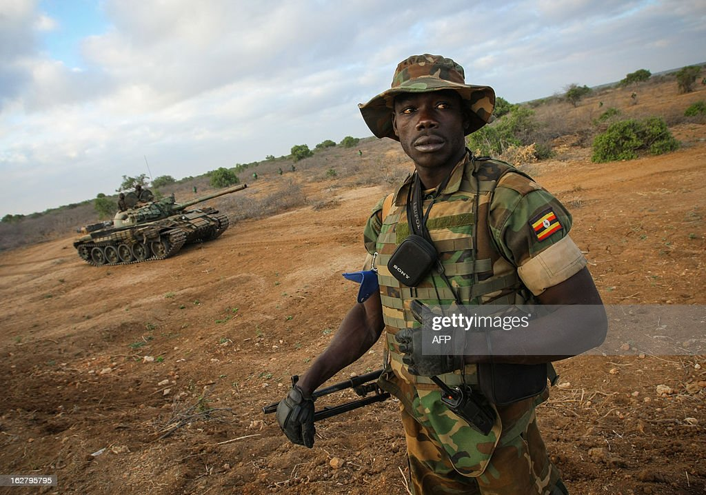 In a handout photograph taken and released by the African Union-United Nations Information Support team on February 27, 2012, a Ugandan soldier serving with the African Union Mission in Somalia (AMISOM) stands on a road during an advance on the central Somali town of Buur-Hakba. The Somali National Army (SNA) supported by AMISOM forces captured the strategically important town on the Afgooye-Baidoa corridor in Bay region from Al-Qaeda-affiliated extremist group Al Shabaab early this morning without any resistance, marking a significant loss for the group. The town, located 64kms east of Baidoa, was a stronghold of the Shabaab where they extorted high levies of illegal taxation on the local civilian populations and used it as a base from where they planned and launched attacks against government forces and installations, AMISOM and the Somali population. Buur-Hakba is the latest in a string of significant territorial losses for the extremist group to SNA and AMISOM forces over the last 18 months, which has seen their area of influence and control over towns and areas across Somalia steadily decrease. AFP PHOTO /AU-UN IST PHOTO / STUART PRICE