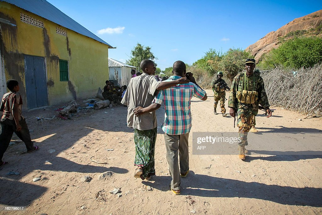 In a handout photograph taken and released by the African Union-United Nations Information Support team 27 February 2012, Somali civilians walk past Ugandan soldiers serving with the African Union Mission in Somalia (AMISOM) in the central Somali town of Buur-Hakba. The Somali National Army (SNA) supported by AMISOM forces captured the strategically important town on the Afgooye-Baidoa corridor in Bay region from Al-Qaeda-affiliated extremist group Al Shabaab early this morning without any resistance, marking a significant loss for the group. The town, located 64kms east of Baidoa, was a stronghold of the Shabaab where they extorted high levies of illegal taxation on the local civilian populations and used it as a base from where they planned and launched attacks against government forces and installations, AMISOM and the Somali population. Buur-Hakba is the latest in a string of significant territorial losses for the extremist group to SNA and AMISOM forces over the last 18 months, which has seen their area of influence and control over towns and areas across Somalia steadily decrease. AFP PHOTO /AU-UN IST PHOTO / STUART PRICE