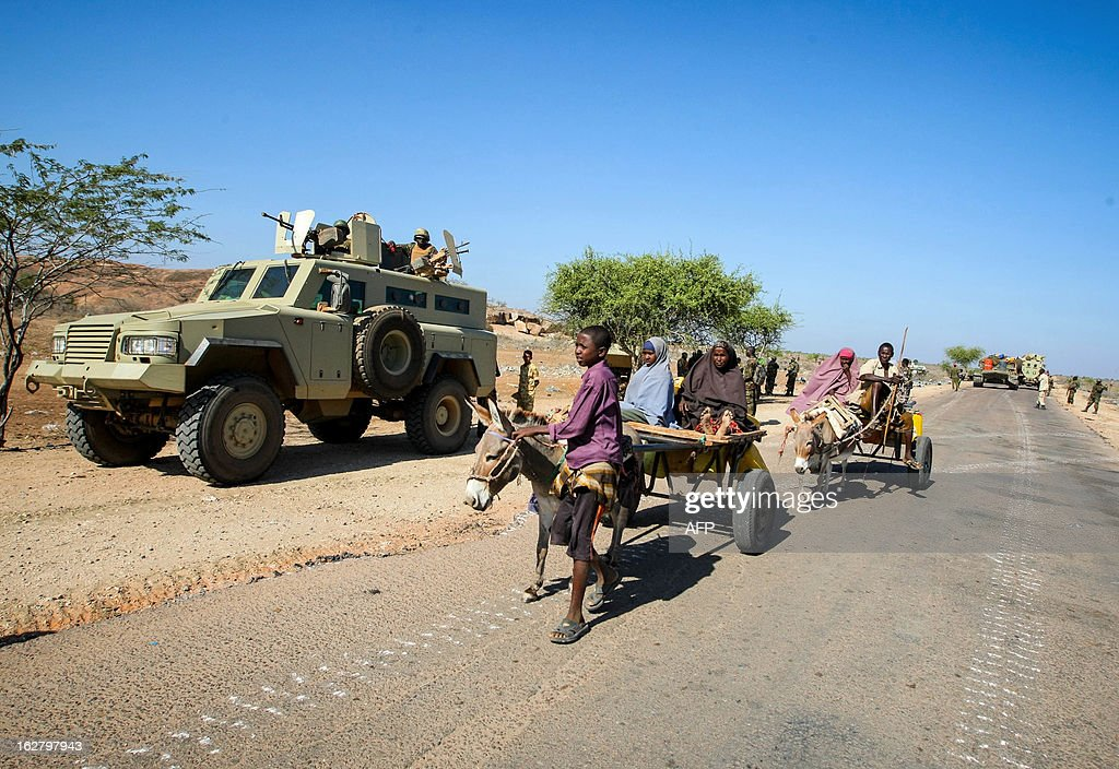 CREDIT 'AFP PHOTO / AU-UN IST PHOTO / STUART PRICE' - NO MARKETING NO ADVERTISING CAMPAIGNS - DISTRIBUTED AS A SERVICE TO CLIENTS In a handout photograph taken and released by the African Union-United Nations Information Support team on February 27, 2013, Somali civilians ride past Ugandan soldiers serving with the African Union Mission in Somalia (AMISOM) in the central Somali town of Buur-Hakba. The Somali National Army (SNA) supported by AMISOM forces captured the strategically important town on the Afgooye-Baidoa corridor in Bay region from Al-Qaeda-affiliated extremist group Al Shabaab early this morning without any resistance, marking a significant loss for the group. The town, located 64kms east of Baidoa, was a stronghold of the Shabaab where they extorted high levies of illegal taxation on the local civilian populations and used it as a base from where they planned and launched attacks against government forces and installations, AMISOM and the Somali population.