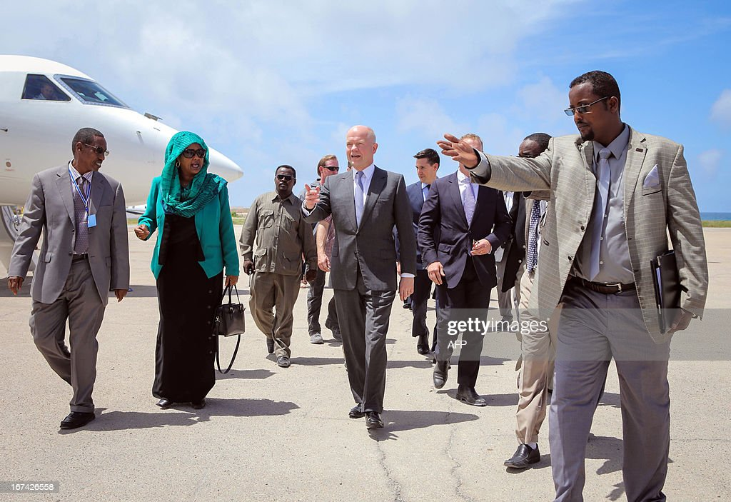 In a handout photograph taken and released by the African Union-United Nations Information Support Team on April 25, 2013, British Foreign Secretary William Hague (C) is directed by a Somali government official as he arrives at Aden Abdulle International Airport in the Somali capital Mogadishu. Britain's Foreign Secretary William Hague on Thursday opened a new embassy in Mogadishu after a 22-year absence, becoming the first EU nation to return to conflict-torn Somalia. Hague raised the Union Jack flag over the new mission at Mogadishu's airport in a surprise visit with Somali President Hassan Sheikh Mohamud. CREDIT 'AFP PHOTO / AU-UN IST PHOTO / STUART PRICE' - NO