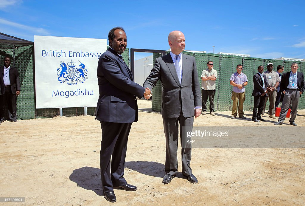 In a handout photograph taken and released by the African Union-United Nations Information Support Team on April 25, 2013, British Foreign Secretary William Hague (C, R) shakes hands with Somali president Hassan Sheikh Mohamud at the opening of the newly built British Embassy in the Somali capital Mogadishu. Britain's Foreign Secretary William Hague on Thursday opened a new embassy in Mogadishu after a 22-year absence, becoming the first EU nation to return to conflict-torn Somalia. Hague raised the Union Jack flag over the new mission at Mogadishu's airport in a surprise visit with Somali President Hassan Sheikh Mohamud. CLIENTS