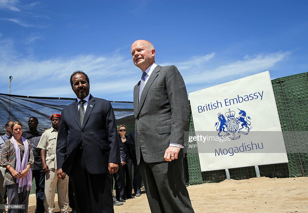 In a handout photograph taken and released by the African Union-United Nations Information Support Team on April 25, 2013, British Foreign Secretary William Hague (R) stands with Somali president Hassan Sheikh Mohamud at the opening of the newly built British Embassy in the Somali capital Mogadishu. Britain's Foreign Secretary William Hague on Thursday opened a new embassy in Mogadishu after a 22-year absence, becoming the first EU nation to return to conflict-torn Somalia. Hague raised the Union Jack flag over the new mission at Mogadishu's airport in a surprise visit with Somali President Hassan Sheikh Mohamud. CLIENTS