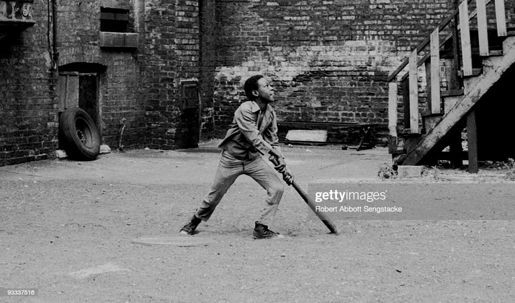 In a makeshift baseball field, dreamed up in the courtyard of an urban apartment building, a young boy looks up to follow the arc of a baseball he has just hit, Chicago, IL, 1970s.