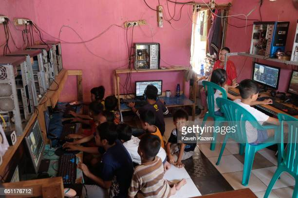 In a makeshift games room slum dweller kids enjoy playing video games on desktop computers in the old town on November 27 2016 in Jakarta Indonesia