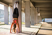 Young female athlete performing handstand outdoors