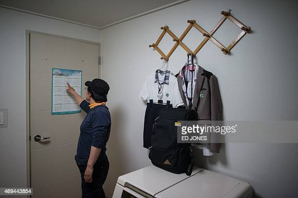 In a photo taken on April 11 2015 Lee GeumHui points to the date of the Sewol ferry disaster on a calendar in the bedroom of her daughter Cho EunHwa...