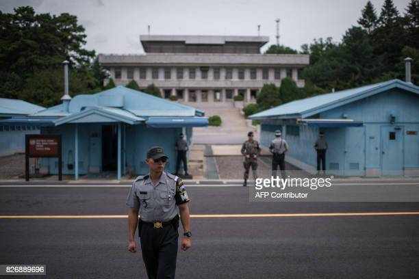 In a photo taken on August 2 2017 South Korean soldiers stand guard before North Korea's Panmon Hall and the military demarcation line separating...