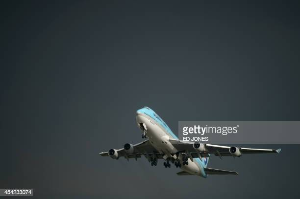 In a photo taken on August 26 2014 a Korean Air Boeing 747 aircraft takes off before storm clouds at Gimpo airport south of Seoul South Korea's...