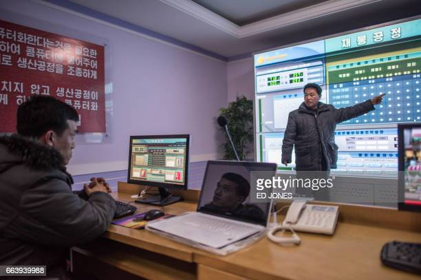 TOPSHOT In a photo taken on February 18 2017 a man gestures as another watches in a control room at the 'Pyongyang Bag Factory' in Pyongyang / AFP...