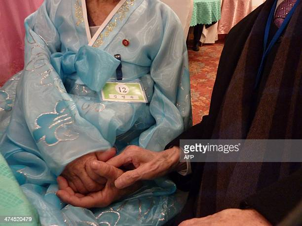 In a photo taken on February 20 2014 South Korean Kim SeRim holds hands with his North Korean sister Kim YoungSook during a family reunion at the...