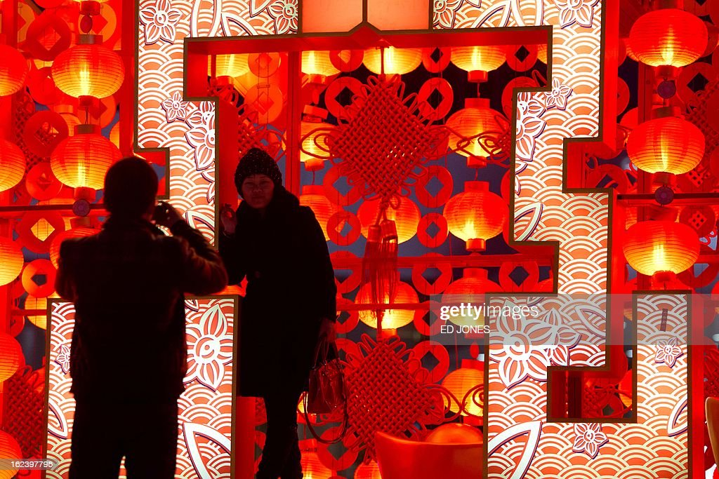 In a photo taken on February 22, 2013 a woman poses for photos next to a lantern display in Beijing. The city is preparing for the traditional Lantern Festival which falls on the 15th day of the Lunar New Year and officially ends the celebrations. AFP PHOTO / Ed Jones