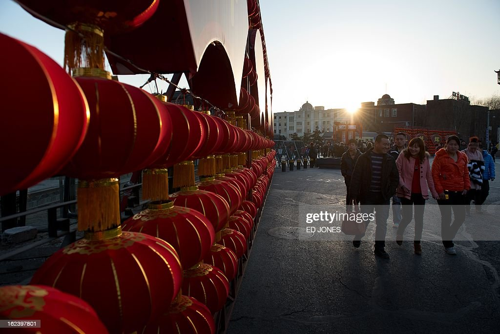 In a photo taken on February 22, 2013 people walk past a lantern display in Beijing. The city is preparing for the traditional Lantern Festival which falls on the 15th day of the Lunar New Year and officially ends the celebrations. AFP PHOTO / Ed Jones