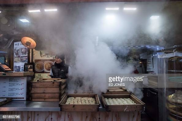 TOPSHOT In a photo taken on January 16 2017 a vendor waits for customers at a stall selling mandu dumplings at a market in Seoul / AFP / Ed JONES