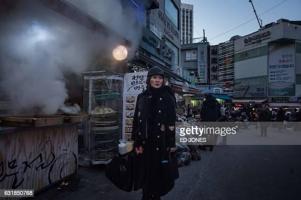 TOPSHOT In a photo taken on January 16 2017 a woman walks through a market in Seoul / AFP / Ed JONES