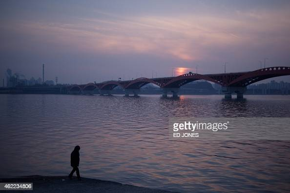 In a photo taken on January 24 2015 a man walks before the Han River and the southern Seoul city skyline during sunset South Korea's economy...