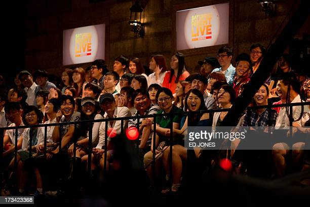 In a photo taken on July 13 2013 audience members laugh during a preview performance of weekly entertainment show Saturday Night Live Korea at a...