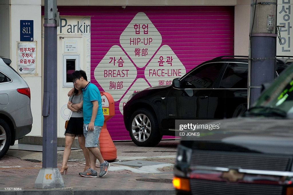 In a photo taken on July 16, 2013 a couple walks past a plastic surgery clinic in Seoul. Skilled plastic surgeons in looks-obsessed South Korea are enjoying an unexpected boom as increasing numbers of foreigners seek aesthetic absolution in what is fast becoming the cosmetic procedure capital of the world. According to government data, overall medical spending by foreign visitors hit a record 116 million US dollars in 2011. Almost a half of all foreigners seeking a nose job, a facelift, a jawbone reduction or a tummy tuck were from China. Their number nearly tripled from 1,657 in 2009 to 4,400 in 2010. Clinics are are also reporting sweilling customer numbers from Japan, the Middle East, Africa, Veitnam, and Mongolia. AFP PHOTO / Ed Jones