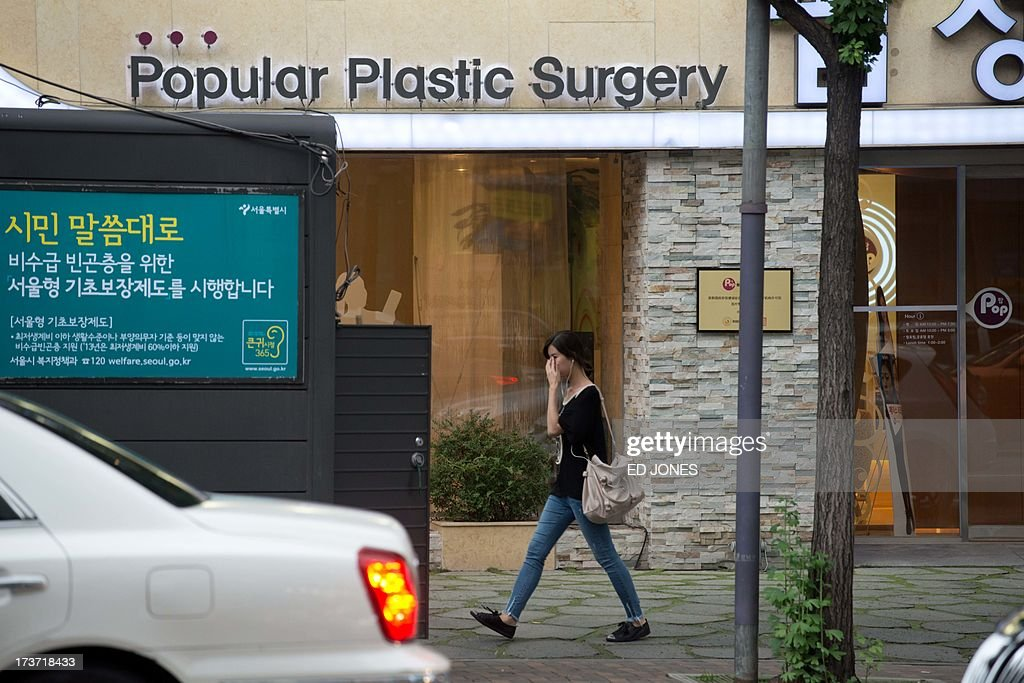 In a photo taken on July 16, 2013 a woman walks past a plastic surgery clinic in Seoul. Skilled plastic surgeons in looks-obsessed South Korea are enjoying an unexpected boom as increasing numbers of foreigners seek aesthetic absolution in what is fast becoming the cosmetic procedure capital of the world. According to government data, overall medical spending by foreign visitors hit a record 116 million US dollars in 2011. Almost a half of all foreigners seeking a nose job, a facelift, a jawbone reduction or a tummy tuck were from China. Their number nearly tripled from 1,657 in 2009 to 4,400 in 2010. Clinics are are also reporting sweilling customer numbers from Japan, the Middle East, Africa, Vietnam, and Mongolia. AFP PHOTO / Ed Jones