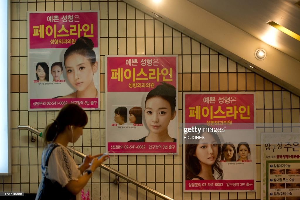 In a photo taken on July 16, 2013 advertisements for plastic surgery clinics are displyed at a subway station in Seoul. Skilled plastic surgeons in looks-obsessed South Korea are enjoying an unexpected boom as increasing numbers of foreigners seek aesthetic absolution in what is fast becoming the cosmetic procedure capital of the world. According to government data, overall medical spending by foreign visitors hit a record 116 million US dollars in 2011. Almost a half of all foreigners seeking a nose job, a facelift, a jawbone reduction or a tummy tuck were from China. Their number nearly tripled from 1,657 in 2009 to 4,400 in 2010. Clinics are are also reporting sweilling customer numbers from Japan, the Middle East, Africa, Veitnam, and Mongolia. AFP PHOTO / Ed Jones