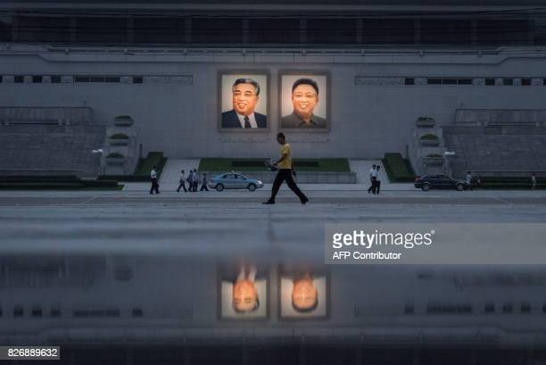 TOPSHOT In a photo taken on July 21 2017 pedestrians and vehicles pass before the portraits of late North Korean leaders Kim IlSung and Kim JongIl in...