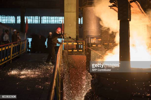 In a photo taken on July 22 2017 a worker checks the temperature of molten steel during production at the Chollima Steel Complex southwest of...