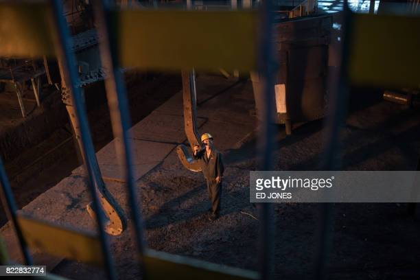 In a photo taken on July 22 2017 a worker guides a bucket of molten steel during production at the Chollima Steel Complex southwest of Pyongyang The...
