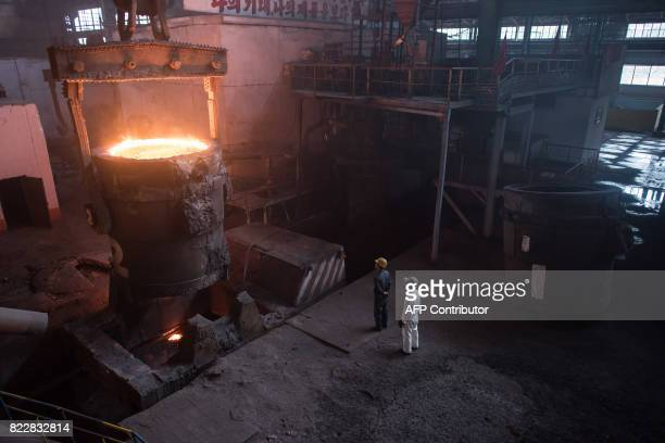 TOPSHOT In a photo taken on July 22 2017 workers watch as molten steel is transfered from a furnace during production at the Chollima Steel Complex...