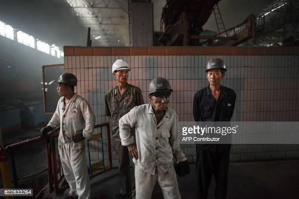 In a photo taken on July 22 2017 workers watch as molten steel is transfered from a furnace during production at the Chollima Steel Complex southwest...
