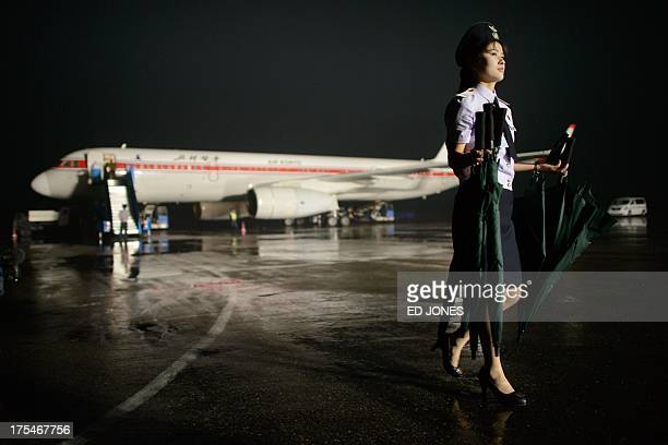 In a photo taken on July 24 2013 a North Korean airport staff member carries umbrellas before an Air Koryo aircraft in Pyongyang North Korea mounted...