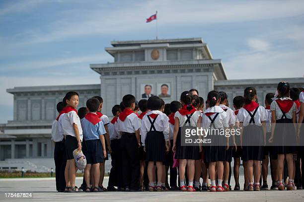In a photo taken on July 25 2013 North Korean school children stand before the portraits of late North Korean leaders Kim IlSung and Kim JongIl at...