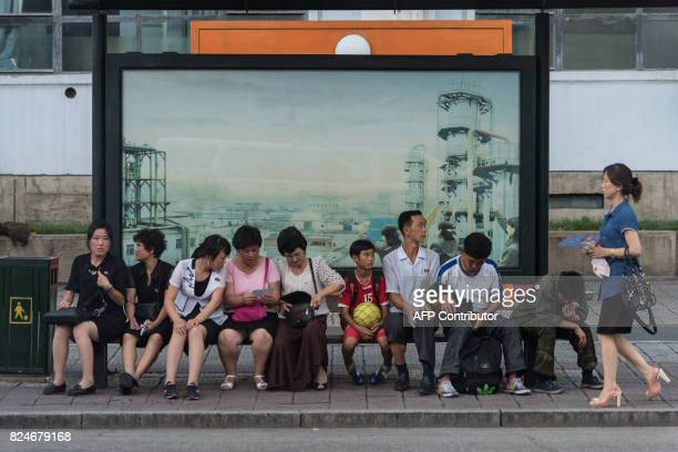 TOPSHOT In a photo taken on July 28 people wait at a trolley bus stop in Pyongyang Buses and trams are by far the most common means of public...