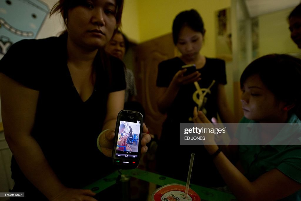 In a photo taken on June 10, 2013 women whose husbands work as miners in the west African country of Ghana display photos taken by their husbands while being detained by Ghanian authorities, at a cafe in the town of Shanglin in southwestern China's Guangxi province. Thousands of men left a poor county in southern China to seek fortunes as gold miners in Africa -- but their families are terrified after deadly clashes and arrests forced many to go into hiding. Men from Shanglin began traveling to Ghana around a decade ago, after mastering mining technology in the 1990s while pioneering the exploitation of gold reserves in China's cold northeast. AFP PHOTO / Ed Jones