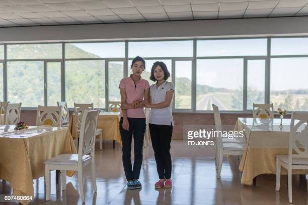 In a photo taken on June 3 2017 vendors and waitstaff Kim HyoJong and Kim UnMi pose for a photo at a rest area on the Pyongyang to Kaesong highway /...