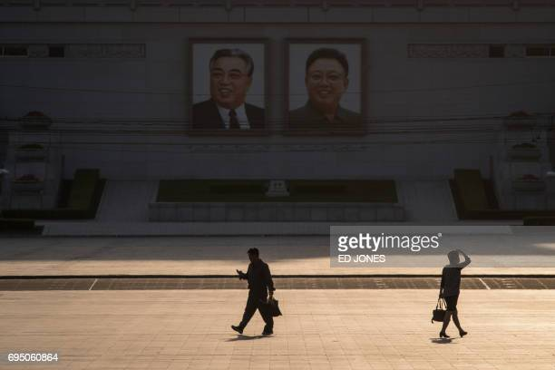 In a photo taken on June 4 2017 a man looks at a mobile phone as he walks past the portraits of late North Korean leaders Kim IlSung and Kim JongIl...