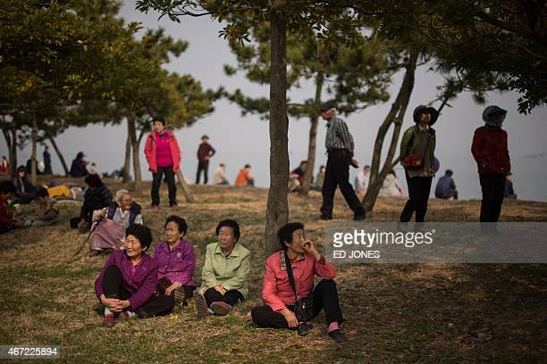 In a photo taken on March 21 2015 a group of elderly people sit as others wait for low tide to walk on a pathway between the South Korean islands of...
