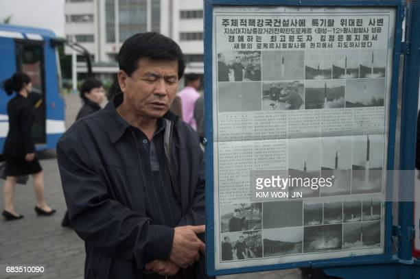 In a photo taken on May 15 2017 a man looks at a streetside newsstand showing a copy of the Rodong Sinmun newspaper featuring coverage of a May 14...